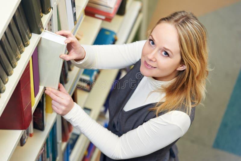 Jeune étudiant adulte choisissant le livre photos libres de droits