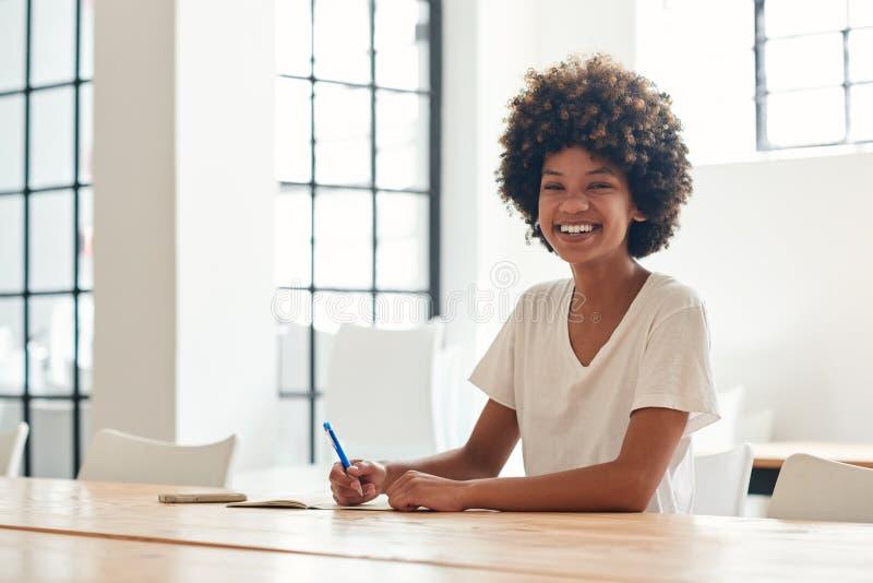 Jeune étudiant africain de sourire seul étudiant à une table de campus photo libre de droits