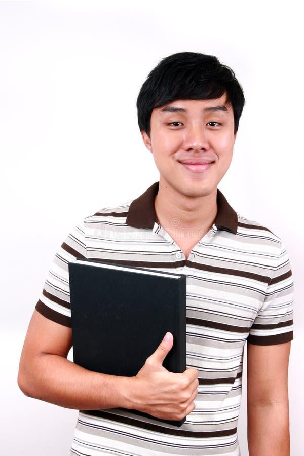 Jeune étudiant asiatique avec des livres à disposition. images stock