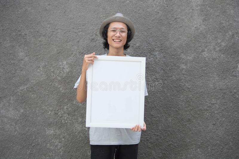 Jeune étudiant asiatique avec des verres et la position de chapeau de chapeau feutré tenant le conseil et le sourire noirs photos libres de droits