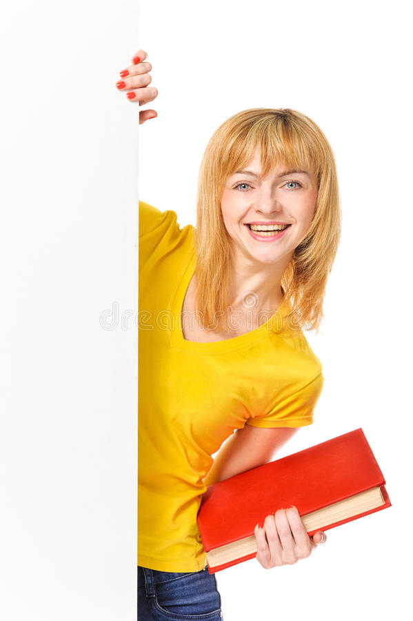 Jeune étudiant avec le livre restant derrière le panneau blanc. D'isolement en fonction photo libre de droits