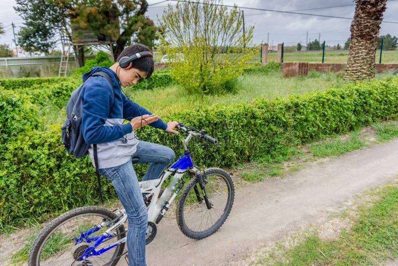 Jeune étudiant avec le sac à dos et la bicyclette, écoutant la musique photos libres de droits