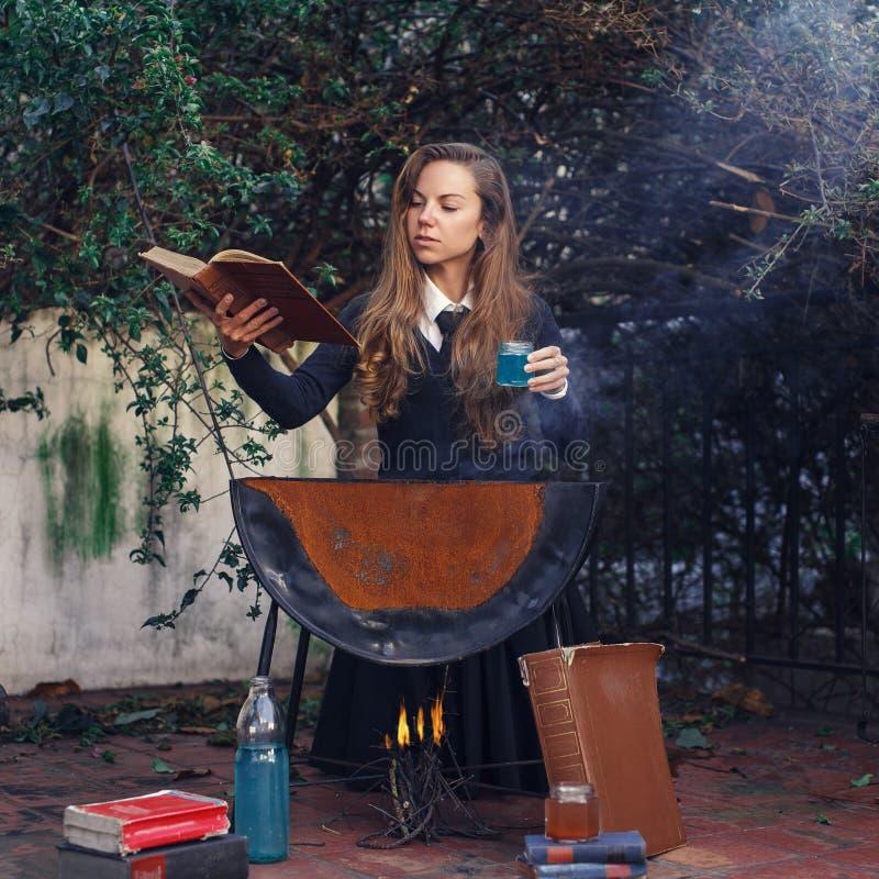 Jeune étudiant d'école magique faisant le poison Helloween photos stock