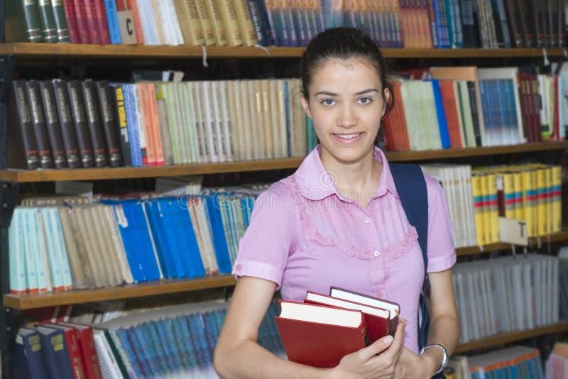 Jeune étudiant dans la bibliothèque photo stock