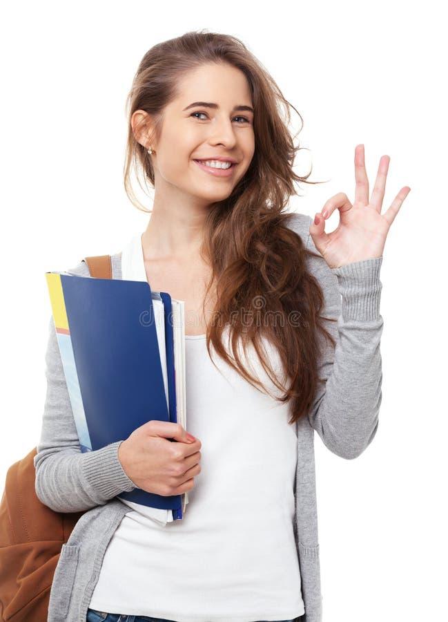 Jeune étudiant heureux montrant le signe correct d'isolement sur le blanc photo stock