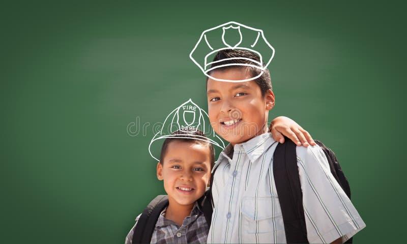 Jeune étudiant hispanique Boy Wearing Backpack Front Of Blackboard avec le casque de pompier et chapeau de policier dessiné dans  images libres de droits
