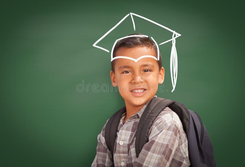 Jeune étudiant hispanique Boy Wearing Backpack Front Of Blackboard avec le chapeau d'obtention du diplôme dessiné dans des frais  photographie stock libre de droits