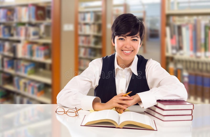 Jeune étudiant In Library de métis avec les livres, le papier et les verres photographie stock
