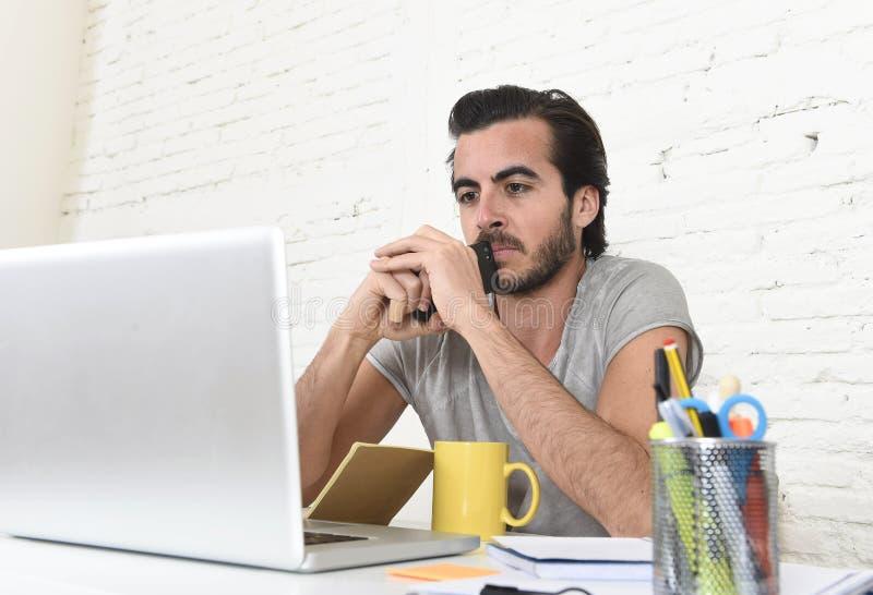 Jeune étudiant ou homme d'affaires moderne de style de hippie travaillant tenant la pensée de téléphone portable photo stock