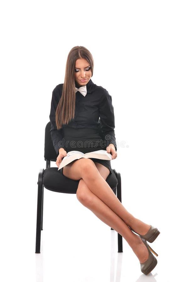 Jeune étudiant s'asseyant sur la chaise avec ses jambes croisées et lisant un livre photos libres de droits