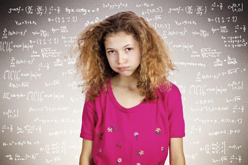 Jeune étudiant soumis à une contrainte se tenant devant un tableau noir rempli photo stock