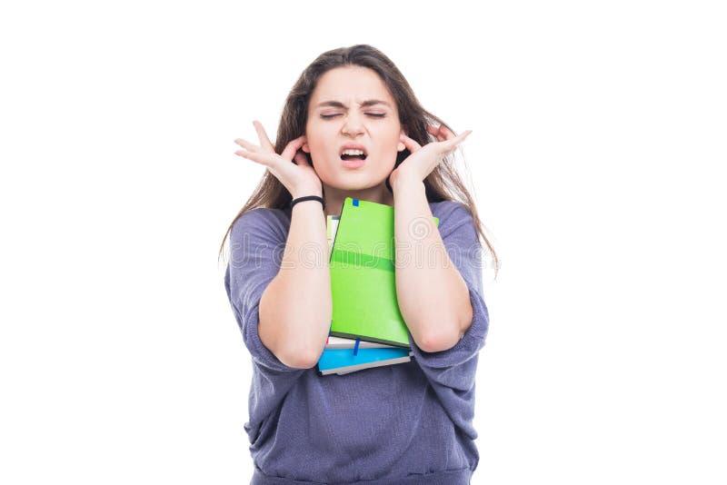 Jeune étudiant universitaire couvrant ses oreilles images libres de droits