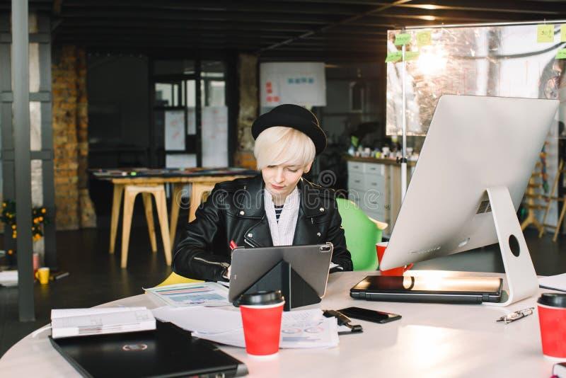 Jeune étudiante à la table utilisant l'ordinateur et le comprimé de technologie reliés au réseau global tout en souriant dedans photographie stock