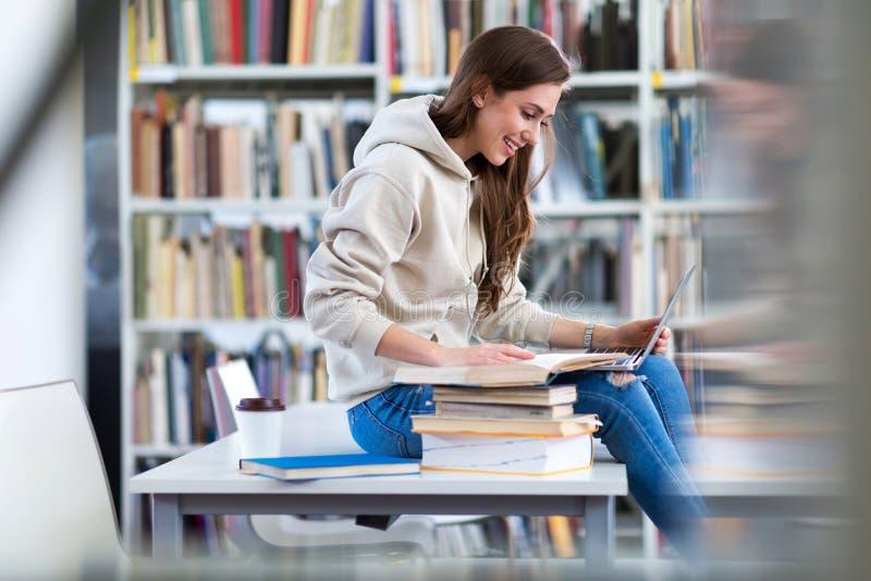 Jeune étudiante étudiant dans la bibliothèque image libre de droits