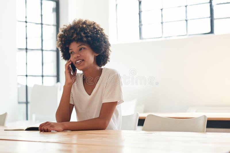 Jeune étudiante africaine de sourire parlant sur son téléphone portable photographie stock libre de droits