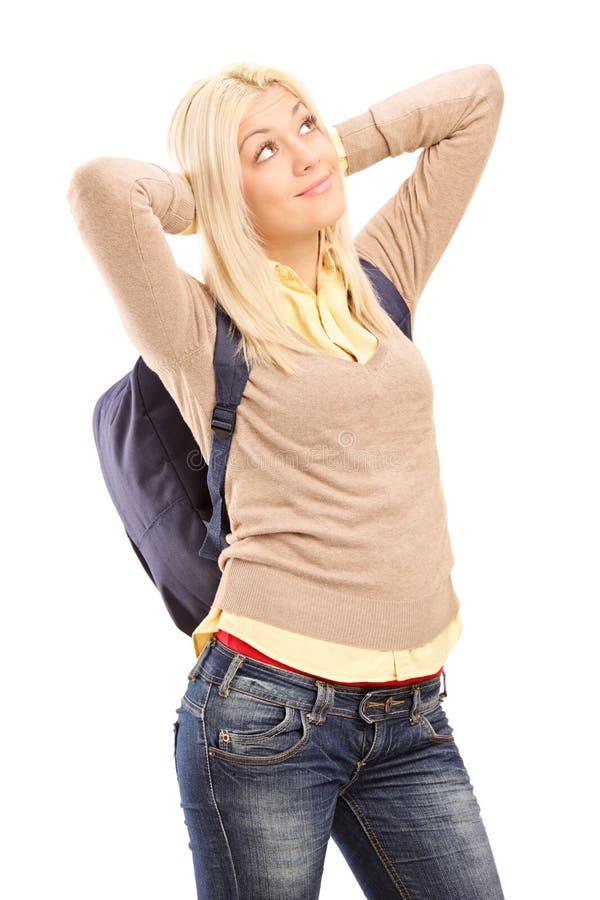 Jeune étudiante avec le sac à dos rêvassant photos stock