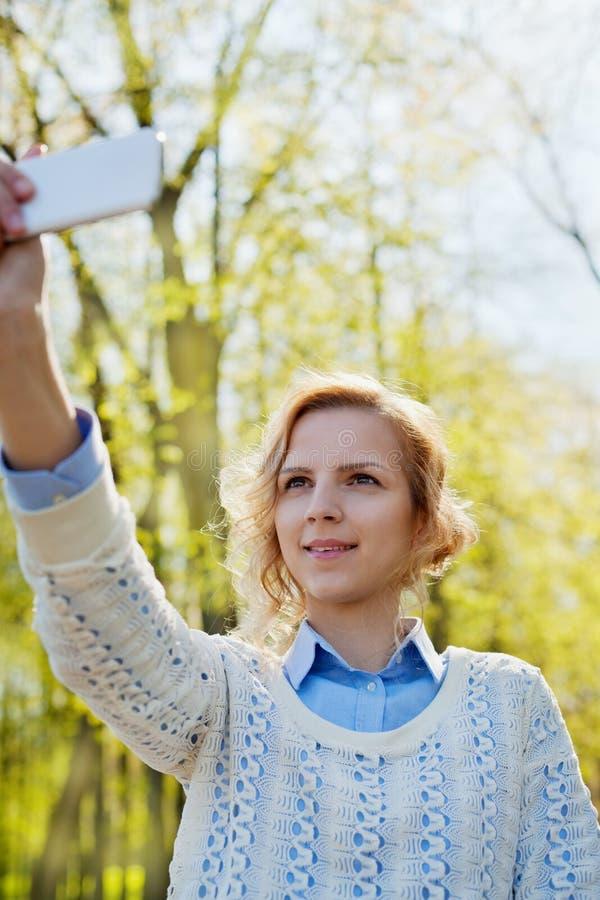 Jeune étudiante ayant l'amusement et prenant la photo de selfie sur l'appareil-photo de smartphone extérieur dans le parc vert da images libres de droits