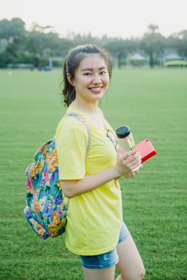Jeune étudiante ayant l'amusement sur le champ d'herbe pendant l'après-midi dans le campus photographie stock