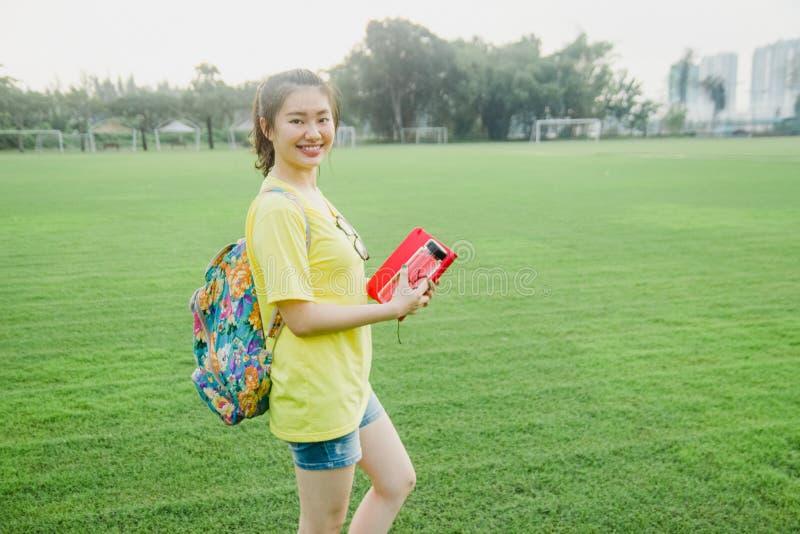 Jeune étudiante ayant l'amusement sur le champ d'herbe pendant l'après-midi dans le campus image stock
