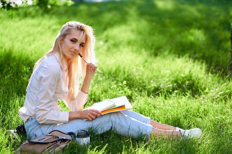 Jeune étudiante blonde avec un livre, un carnet et un stylo sur le pré Préparation à partir de session et d'examens Verticale ext image stock