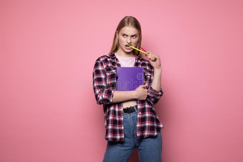 Jeune ?tudiante blonde dans des v?tements sport tenant le carnet et le stylo pourpres dans sa bouche images stock