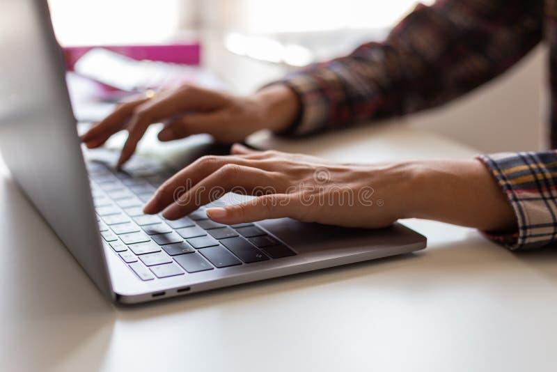 Jeune étudiante dactylographiant sur l'ordinateur se reposant à la table en bois image libre de droits
