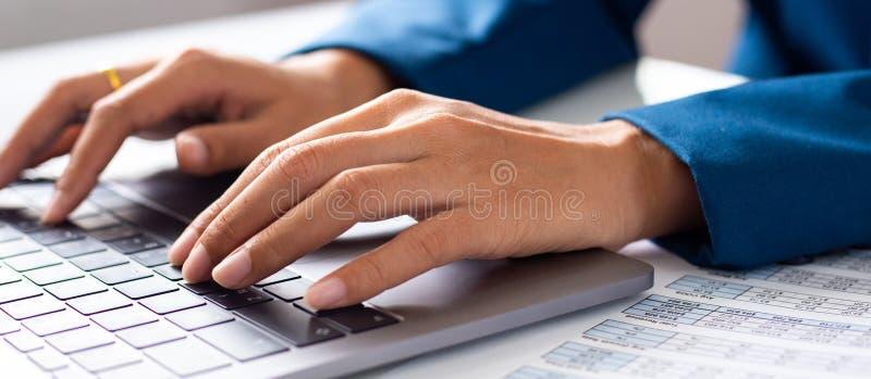 Jeune étudiante dactylographiant sur l'ordinateur se reposant à la table en bois images libres de droits