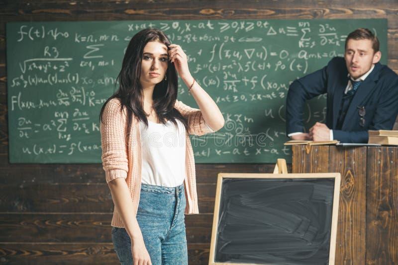 Jeune étudiante dans le cardigan rose et blues-jean se tenant devant le conseil vert Adolescente de brune dans photos libres de droits