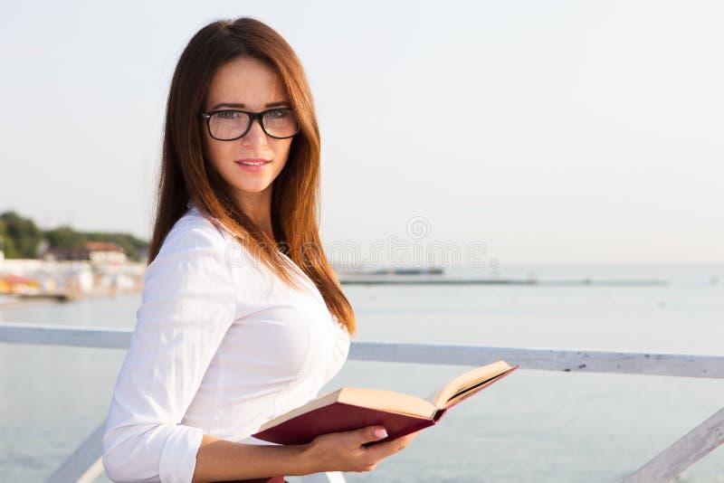 Jeune étudiante en verres de lecture avec le livre images libres de droits