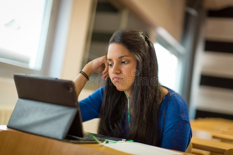 Jeune étudiante ennuyée à la salle de classe d'université Elle ` s utilisant le comprimé et les écouteurs pour prendre des notes photographie stock
