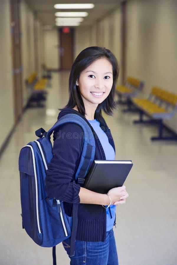 Jeune étudiante féminine asiatique dans la robe d'obtention du diplôme, d'isolement sur le fond blanc photo stock