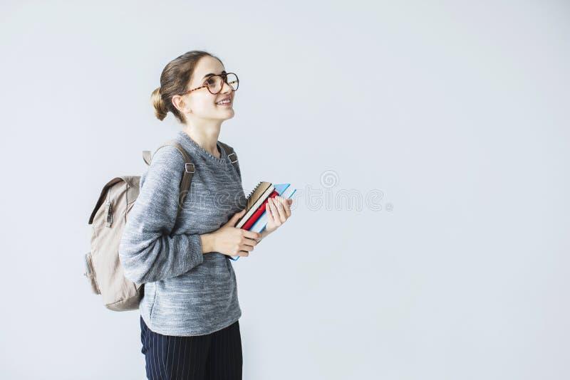 Jeune étudiante heureuse regardant le sac à dos vers le haut de transport tenant des livres photo stock