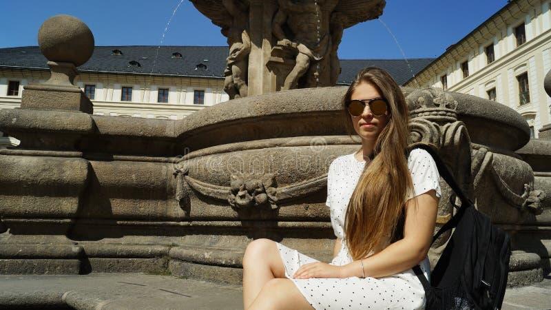 Jeune étudiante posant par la fontaine un jour ensoleillé dans le château de Prague à Prague photo stock