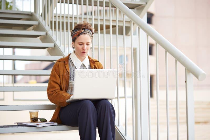 Jeune étudiante rousse de hippie à l'aide de l'ordinateur dehors photos libres de droits