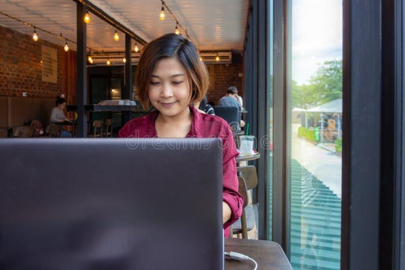 Jeune étudiante s'asseyant à la table et dactylographiant sur l'ordinateur portable photo libre de droits