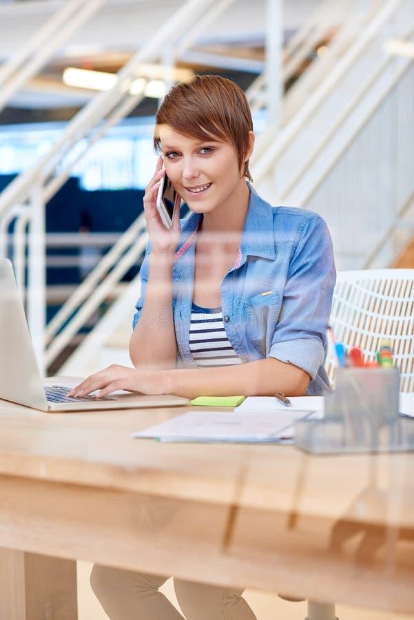 Jeune étudiante souriant au bureau utilisant le téléphone et l'ordinateur portable images libres de droits