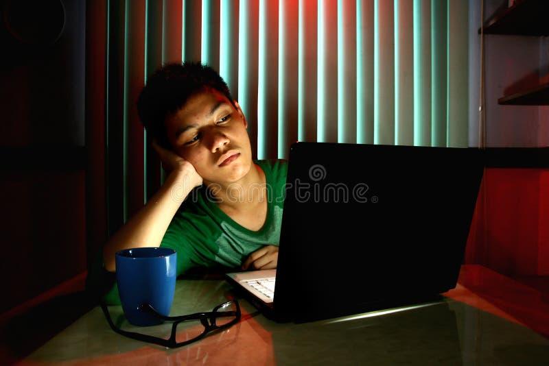 Jeune adolescent avec des lunettes et ennuyé devant un ordinateur portable image stock
