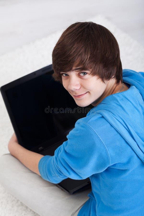Jeune adolescent avec l'ordinateur portatif photographie stock libre de droits