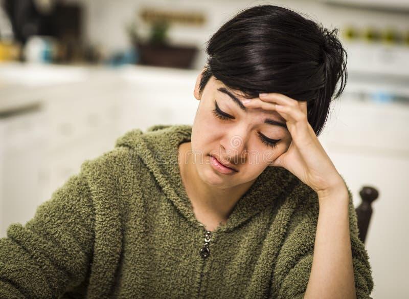 Jeune adolescent déprimé de métis seul se reposant dans la cuisine photographie stock libre de droits
