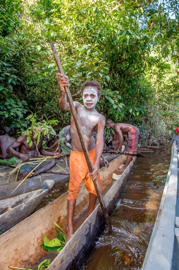 Jeune adolescent de tribu d'Asmat avec l'aviron sur le canoë photos stock