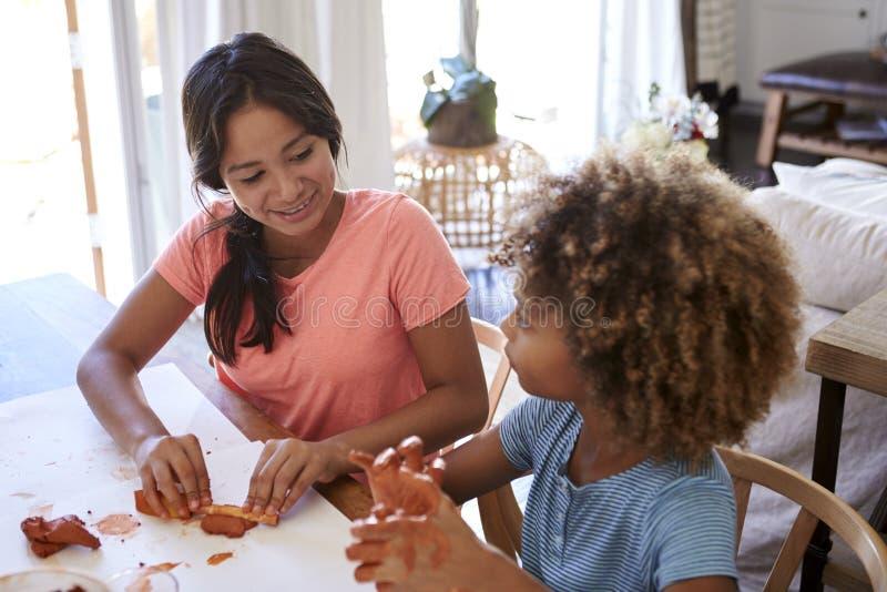 Jeune adolescent deux et amies de la préadolescence s'asseyant à une table à la maison jouant avec modeler l'argile, étroitement, photographie stock libre de droits