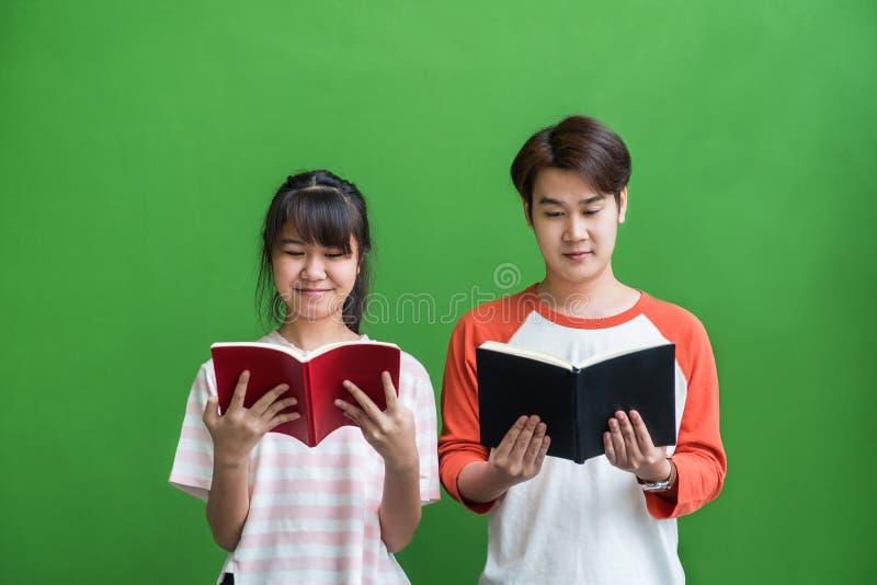 Jeune adolescent et position et lecture de fille au livre au vert photographie stock