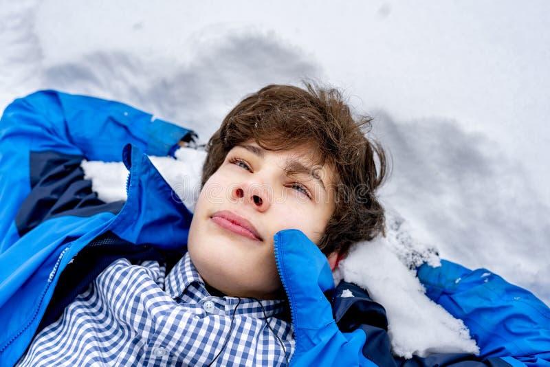 Jeune adolescent masculin dans le mensonge occasionnel sur la neige un jour f d'hiver photo libre de droits