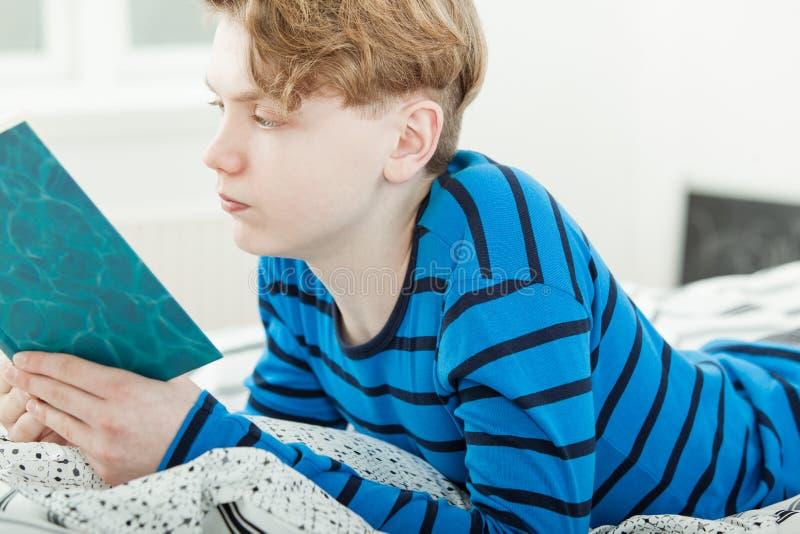 Jeune adolescent studieux lisant un livre images stock