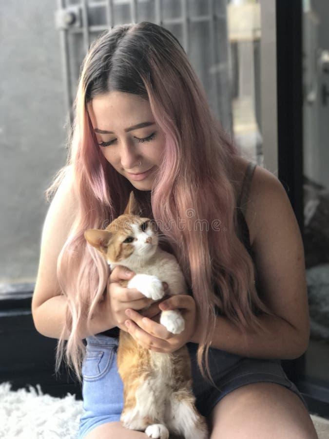 Jeune adolescente avec de longs cheveux tenant des chats d'animal familier photos libres de droits