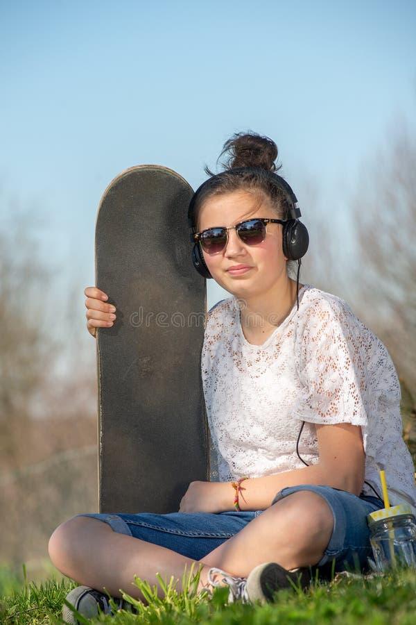 Jeune adolescente avec la planche à roulettes image stock