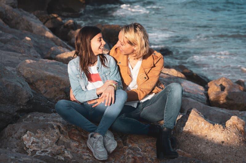 Jeune adolescente avec sa mère dans le geste affectueux par la mer Vacances de famille sur la côte images libres de droits