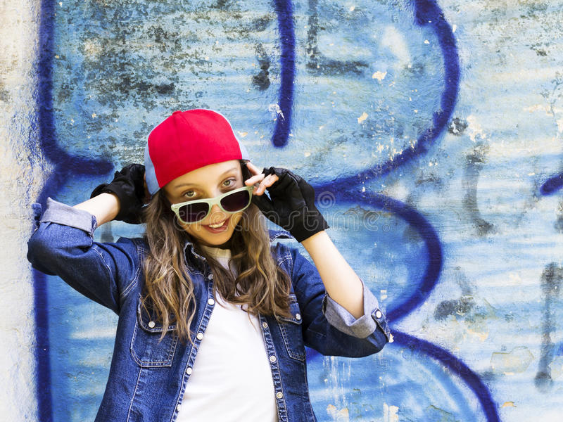 Jeune adolescente blonde mignonne de fille dans une chemise de casquette de baseball et de denim sur un fond de mur en pierre photo stock