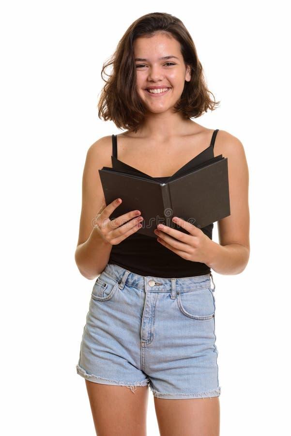 Jeune adolescente caucasienne heureuse souriant tout en tenant le livre images stock
