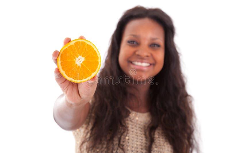 Jeune adolescente d'Afro-américain retenant une orange coupée en tranches photos stock